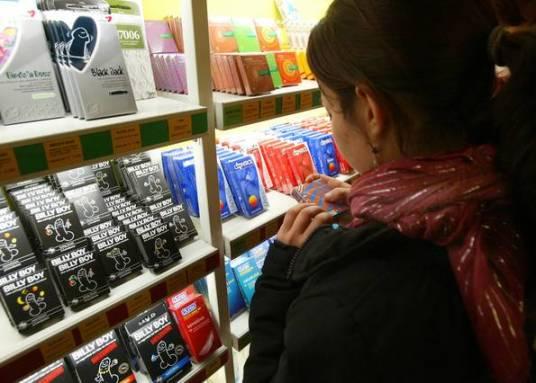 Una chica, frente a un estante repleto de preservativos en una tienda especializada de Barcelona.